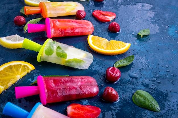 Popsicle de fruits lumineux fait maison avec fraise, cerise, citron, orange, citron et menthe et fruits frais pour la crème glacée sur une surface bleu foncé