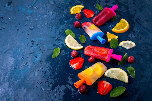 Popsicle de fruits lumineux multicolore avec fraise, cerise, citron, orange, citron et menthe et tranches de fruits frais sur un bleu foncé