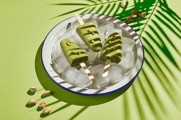 Popsicle maison congelé à la pistache dans un bol de glace sur fond vert avec ombre de feuille de palmier