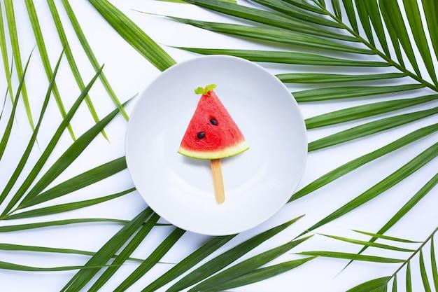 Popsicle tranche de pastèque dans une assiette blanche sur des feuilles de palmiers tropicaux