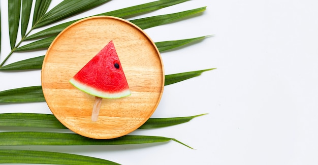 Popsicle tranche de pastèque sur plaque de bois sur des feuilles de palmiers tropicaux