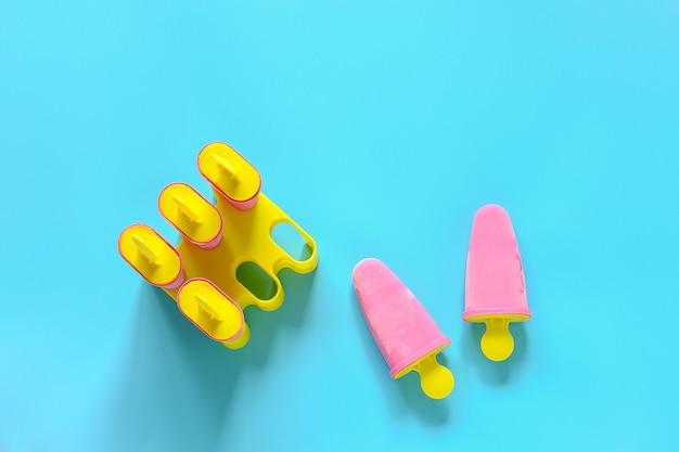 Popsicles maison. glace à la fraise naturelle dans des moules en plastique brillant sur mur bleu
