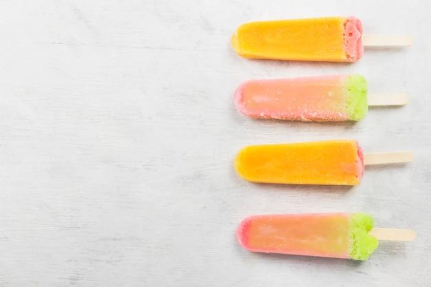 Popsicles multicolores sur fond blanc.
