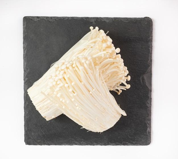 Populaire dans la cuisine asiatique, champignon à l'aiguille d'or frais ou enoki, enokitake. vue de dessus. mise à plat. fraîchement du jardin biologique de croissance à domicile. concept de nourriture.