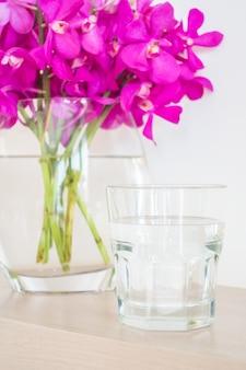 Por fleurs et un verre d'eau à proximité