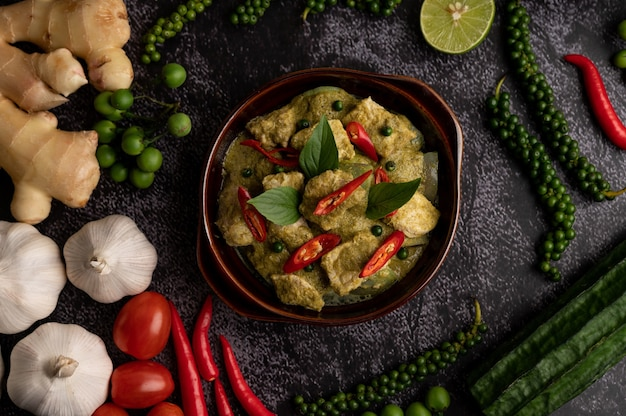Porc au curry vert dans un bol brun avec des épices sur un fond de ciment noir