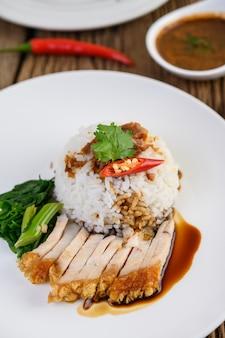 Porc croustillant sur une assiette blanche garnie de sauce et de piment fendu en deux.