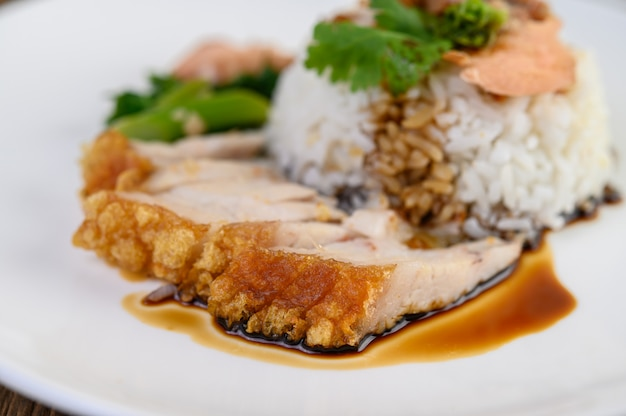 Porc croustillant sur une plaque blanche garnie de sauce.