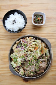 Porc de cuisine japonaise au gingembre sur une poêle en fond de bois