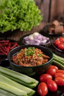 Porc doux dans un bol noir, avec concombres, haricots longs, tomates et accompagnements