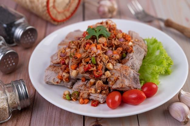 Porc épicé haché avec des tomates et de la laitue sur une plaque blanche sur une table en bois.