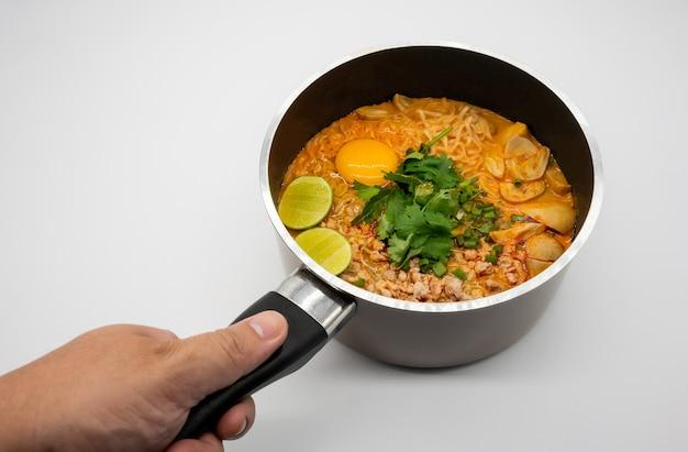 Porc épicé 'tom yum' avec soupe de nouilles instantanées dans un pot chaud isolé sur une surface blanche. cuisine thaïlandaise célèbre.