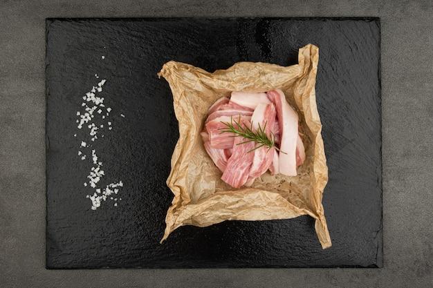 Le porc est empilé sur du papier et une fourchette et une poivrière sont également placées