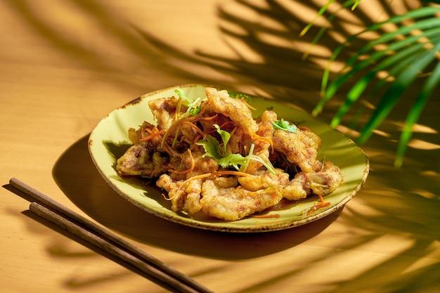 Porc frit en pâte avec carottes et concombres avec sauce aigre-douce. cuisine chinoise