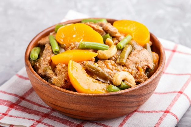 Porc frit avec des pêches, des noix de cajou et des haricots verts dans un bol en bois sur un fond de béton gris