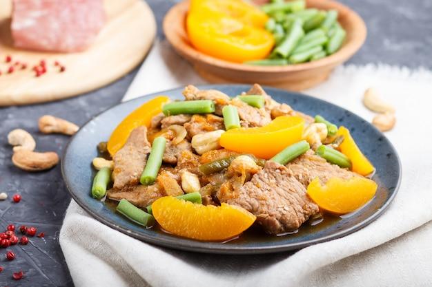 Porc frit avec des pêches, des noix de cajou et des haricots verts sur un fond de béton noir