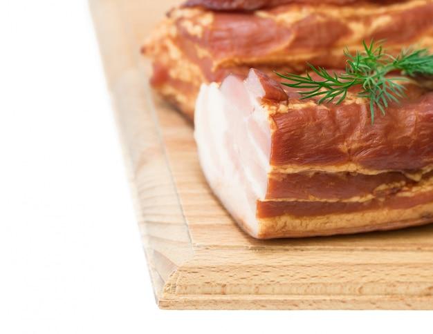 Porc fumé aux épices sur une planche de bois isolée sur blanc.