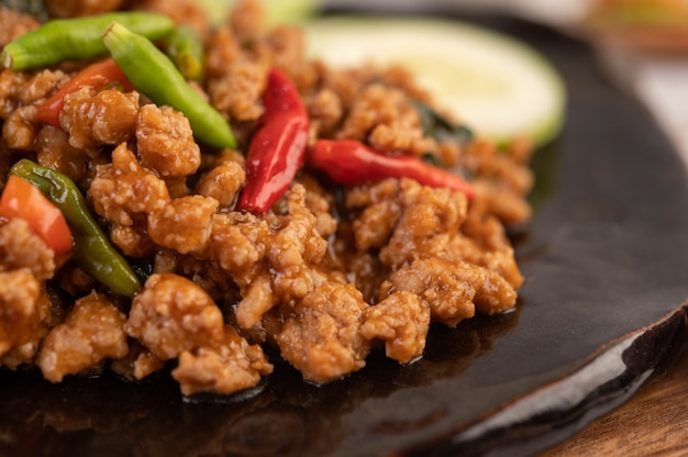 Porc haché épicé et riz sur une plaque noire.