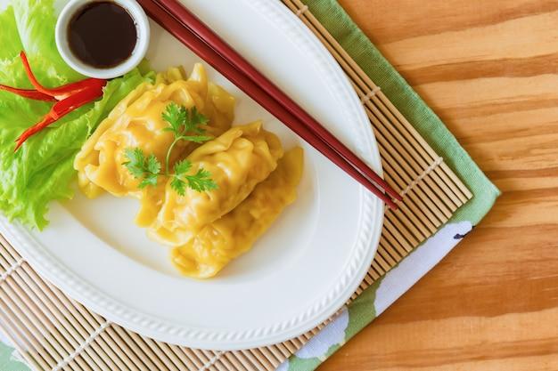 Porc haché maison ou boulette de crevettes dim sum et trempette sauce soja sur table en bois.
