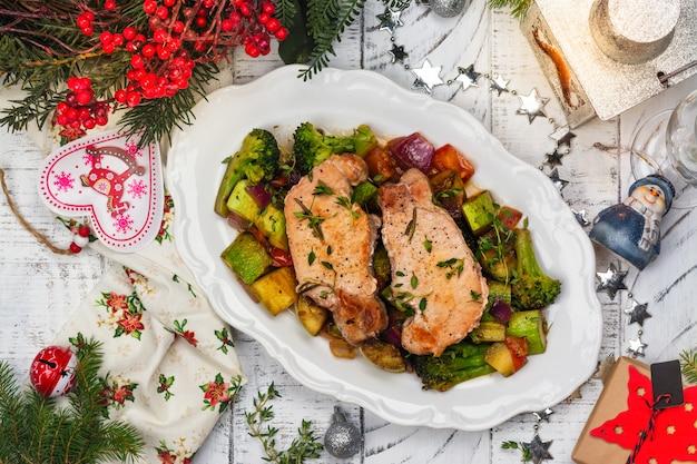 Porc rôti de noël avec des légumes. table décorée de noël