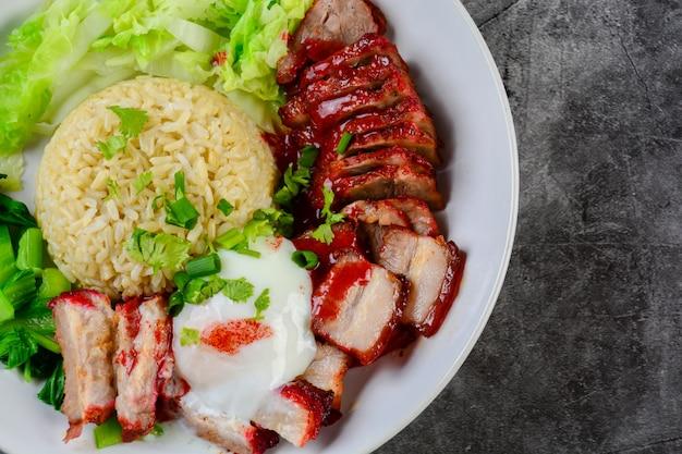 Porc rouge au barbecue et au porc croustillant à la sauce rouge, servi avec du riz et des légumes sur une plaque blanche,
