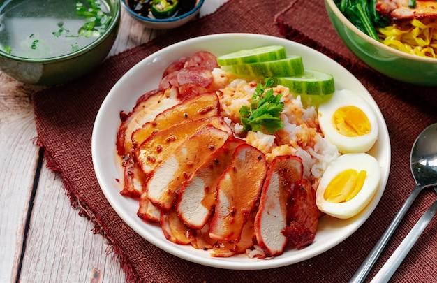 Porc rouge grillé avec riz servi avec œuf à la coque, saucisse, soupe et sauce sucrée