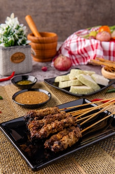 Porc satay ou sate babi porc satay servi avec une sauce aux arachides et des tranches de galettes de riz lontong ou ketupat