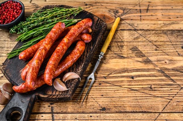 Porc saucisses fumées avec ajout d'herbes aromatiques fraîches et d'épices. fond en bois. vue de dessus. espace de copie.
