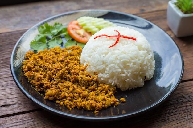 Le porc sauté avec de la pâte de curry jaune sur du riz est sur une plaque noire et un fond de bois brun