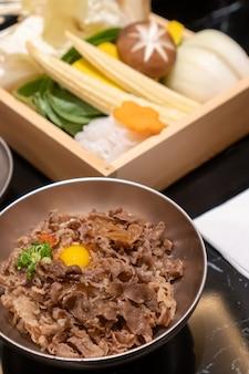 Porc sauté en tranches avec sauce sucrée garni de riz japonais avec un œuf de plume dans un petit bol en acier inoxydable et divers aliments frais.