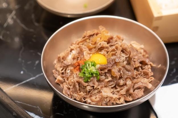 Porc sauté en tranches avec sauce sucrée garni de riz japonais avec un œuf de plume dans un petit bol en acier inoxydable