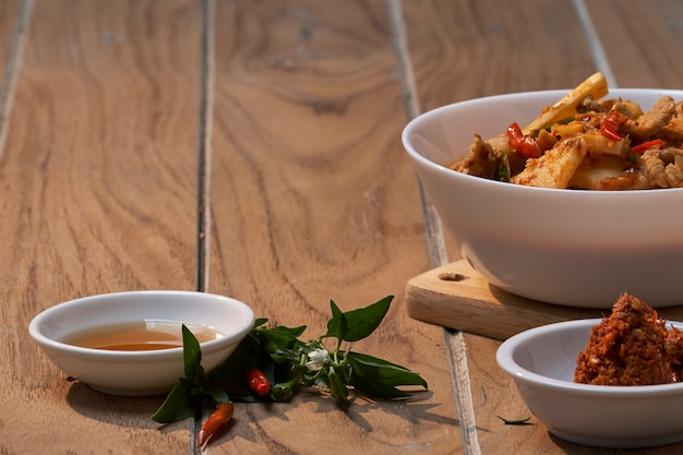 Porc savoureux au curry rouge avec une tranche de bambou sur fond de bois, cuisine thaïe originale