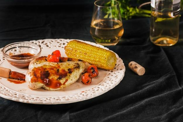 Porc servi avec des tomates cerises et corncob sur plaque