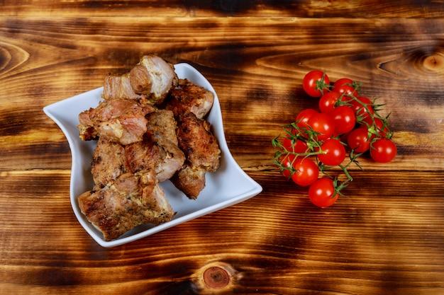 Porc shashlyk sur des brochettes sur une planche de bois sombre avec des tomates, des épinards et des sauces