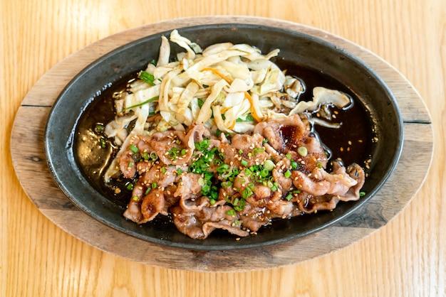 Porc teriyaki dans une poêle chaude avec du chou - style de cuisine japonaise