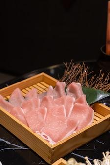 Porc tranché frais non cuit mis dans une boîte carrée en bois qui se prépare pour shabu