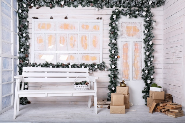 Porche décoratif avec décoration de noël dans les tons blancs avec une guirlande