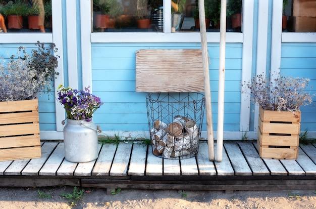 Porche de maison en bois avec bois de chauffage, fleurs.