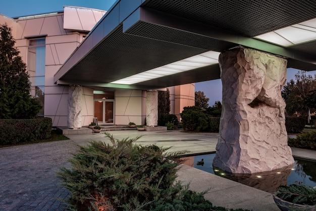 Porche de maison de campagne de luxe soutenu par une colonne en pierre dans une piscine éclairée avec des canards flottants