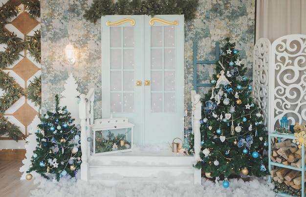 Porche avec porte en décorations de noël et arbres de noël. guirlandes d'épicéa autour de la porte.