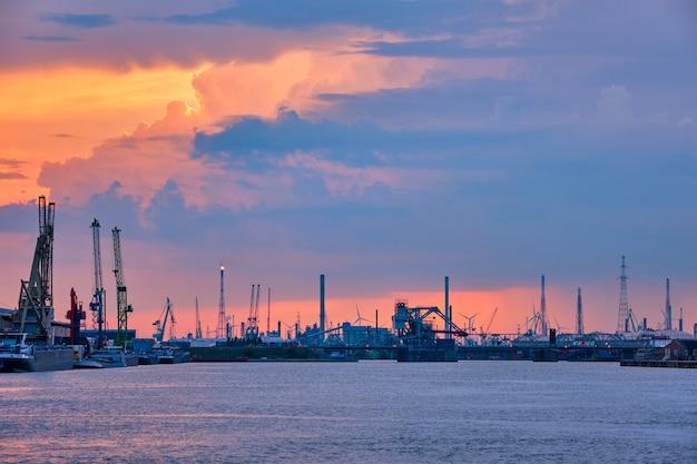 Port d'anvers avec des grues portuaires au crépuscule