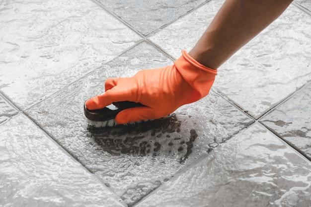 Le port de gants en caoutchouc orange est utilisé pour convertir le nettoyage des gommages sur le carrelage.