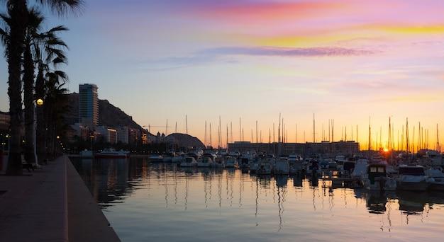 Port avec yachts et remblai au lever du soleil. alicante