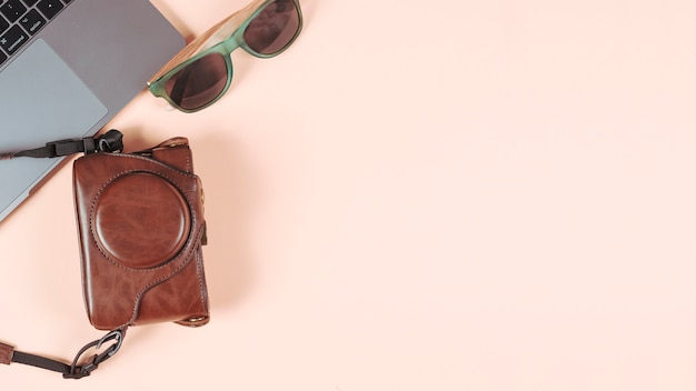 Portable; lunettes de soleil et appareil photo dans son étui sur fond de couleur unie
