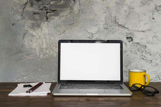 Portable; lunettes; tasse; crayon; bloc-notes en spirale et clip bouledogue sur un bureau en bois