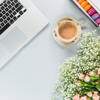 Portable; tasse à café; macarons et bouquet de fleurs sur fond blanc