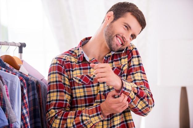 Portant sa chemise préférée. beau jeune homme portant une chemise et parlant au téléphone mobile