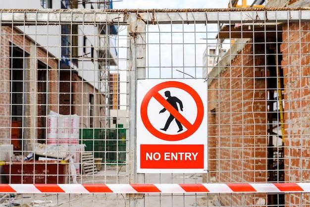 Porte d'accès fermée au chantier de construction d'un immeuble, avec un panneau d'interdiction d'entrée