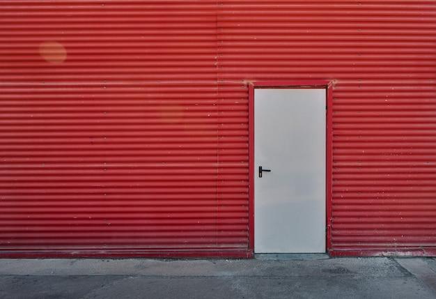 Porte blanche dans un mur rouge