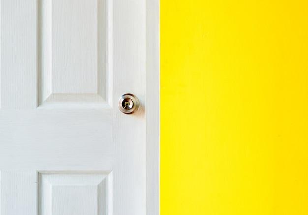 Porte blanche et mur de briques jaunes.